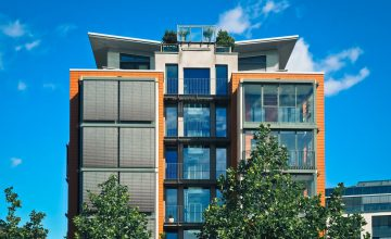 fotografia przedstawia nowoczesny blok. Front od podstawy budynku aż po dach cały przeszklony.
